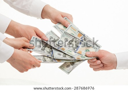 Business people taking money from businessman's hand, white background - stock photo