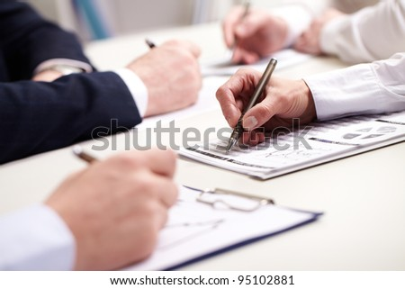 Business people taking notes at briefing - stock photo
