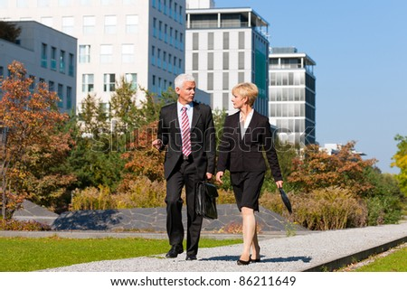 Business people talking outdoors and walking in a park - stock photo