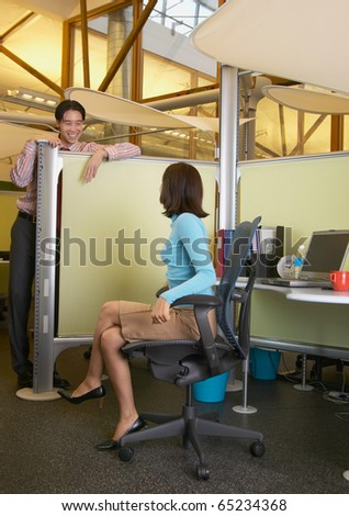 Business people talking over cubicle wall - stock photo