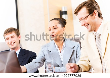 Business people talking, sitting at the table, watching the presentation on a laptop - stock photo