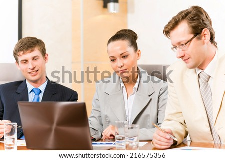 Business people talking, sitting at the table, watching the presentation on a laptop
