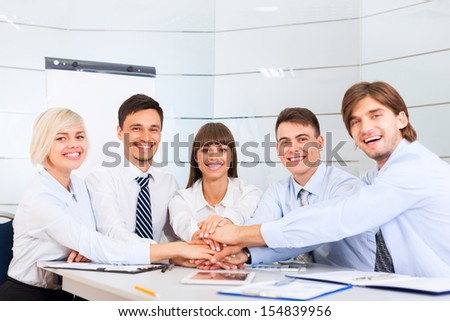 Business people team at office meeting, group of smile businesspeople leader hold pile of hands putting on top of each other on desk, concept of collaboration, working together cooperation - stock photo