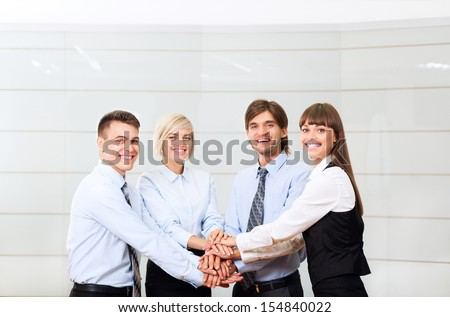 Business people team at office meeting, group of smile businesspeople leader hold pile of hands putting on top of each other, concept of collaboration, working together cooperation