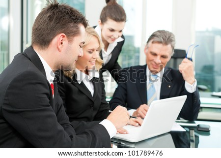 Business people - team meeting in an office with laptop, the boss with his employees