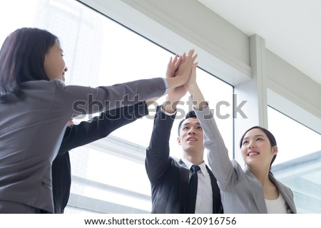 Business people team smile give high five in the office, shot in Hong Kong, asian woman and man - stock photo