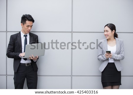 Business people team use smart phone and computer in the office, shot in Hong Kong, asian woman and man - stock photo