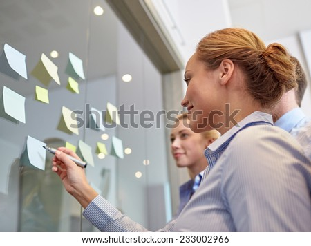 business, people, teamwork and planning concept - smiling business team with marker and stickers working in office - stock photo