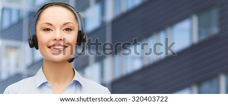 business, people, technology and communication concept - happy asian female helpline operator in headset over city office building background - stock photo