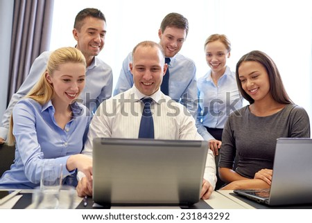 business, people, technology and communication concept - smiling business team with laptop computer making video conference in office