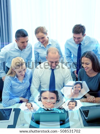 business, people, technology and teamwork concept - smiling business team with laptop computer and virtual projection working in office
