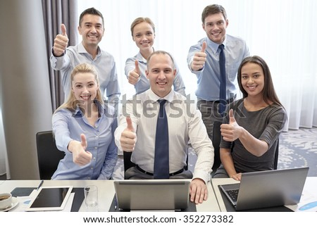 business, people, technology, gesture and teamwork concept - smiling business team with laptop computers showing thumbs up in office - stock photo