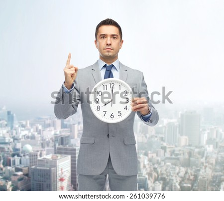 business, people, time management and gesture concept - businessman in suit holding clock showing 8 o'clock and pointing finger up over city background - stock photo