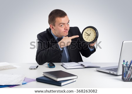 Business, people, time management and office concept - Businessman in suit holding clock showing a time on gray background - stock photo