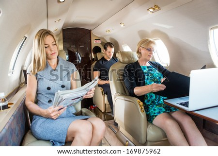 Business people traveling in corporate jet - stock photo