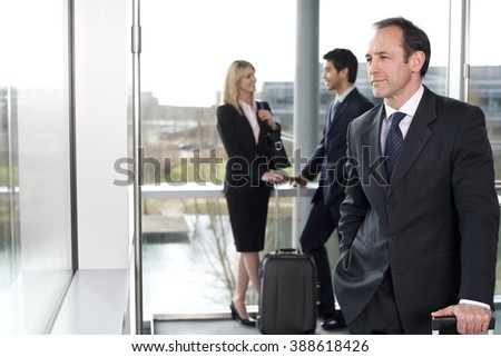 Business people traveling, waiting in airport or station - stock photo