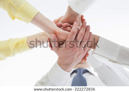 Business people uniting their hands - gesture of a union, view from below - stock photo