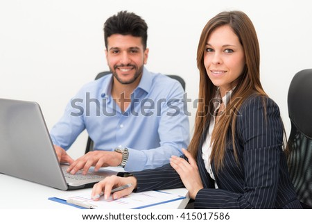 Business people using a laptop computer in their office