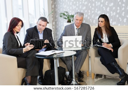 Business people using laptop and talking about a work - stock photo