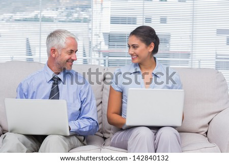 Business people using their laptops and smiling at each other on sofa in staffroom - stock photo