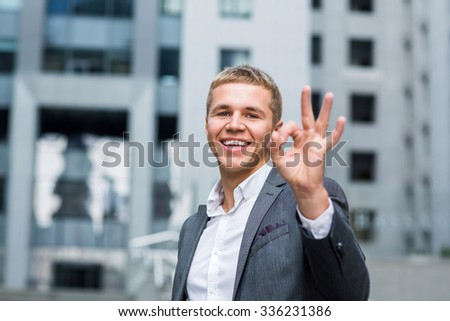 business, people, vision and success concept - happy smiling businessman in eyeglasses and suit showing ok sign over office building background - stock photo