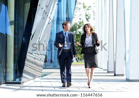 Business people walking and talking in the street - stock photo