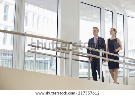 Business people walking by railing in office - stock photo
