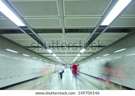 business people walking in metro station tunnel for transfer - stock photo