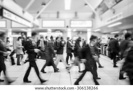 business people walking in the subway station. motion blurred black and white filter - stock photo