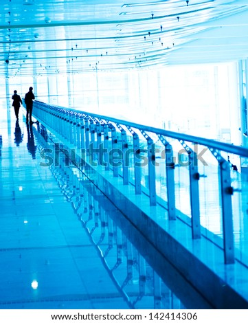 business people walking in the tunnel of modern building. - stock photo