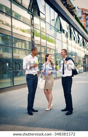 Business people walking standing in front of their office, looking each other and smiling. Their are at coffee break. Shallow depth of field. - stock photo
