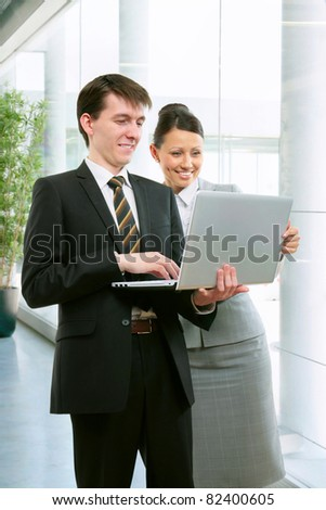 Business people with a laptop in an office corridor - stock photo