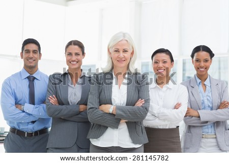 Business people with arms crossed smiling at camera in office