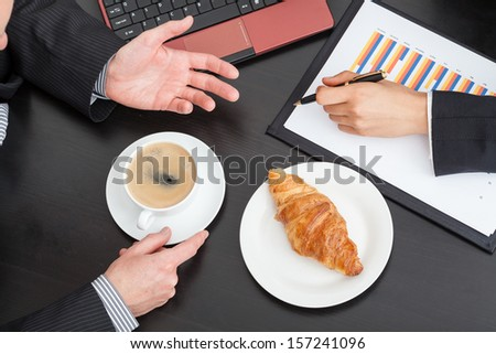 Business people with coffee and croissant at the meeting