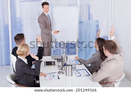 Business people with hands raised answering businessman in meeting at office