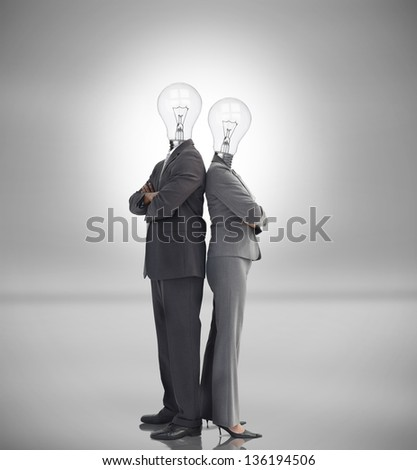 Business people with light bulbs instead of heads standing back to back - stock photo