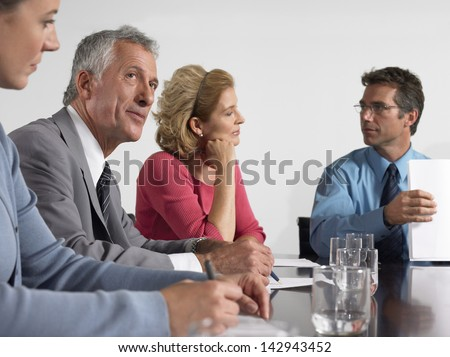 Business people with paperwork during meeting in conference room - stock photo
