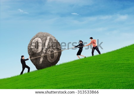 Business people work together trying to get a percentage stone uphill