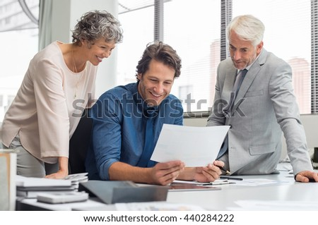 Business people working as a team at office. Business partners discussing documents and ideas during meeting. Team of businesmen and senior businesswoman feeling happy after seeing final contract.  - stock photo
