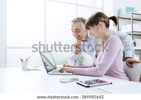 Business people working at office desk, a woman is using a laptop and her chief is watching the computer screen - stock photo