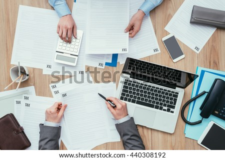 Business people working at office desk, they are checking tax forms and calculating costs, finance and management concept - stock photo