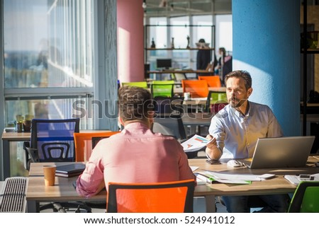 Business people working at table in front of laptop computers in board room in office. Two men discussing new business project for their company, firm, enterprise.