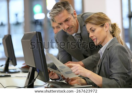 Business people working in office on desktop computer