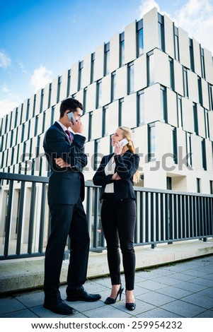 Business people working outdoors in city on bridge in front of office building - stock photo