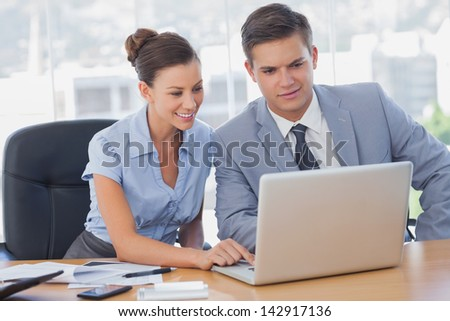 Business people working together on laptop and smiling in the office - stock photo