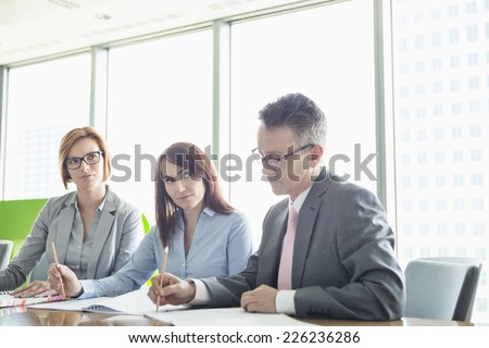 Business people writing on books at conference table - stock photo