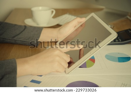 Business person analyzing financial statistics displayed on the tablet screen with vintage style - stock photo