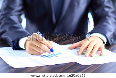 business person analyzing graphs and taking notes - stock photo