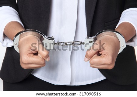 Business person arrested for fraud. Person wearing formal wear in hand cuffs against a white background - stock photo