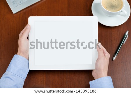 Business person holding a tablet with an empty screen over a desk with a cup of coffee, and pen and a calculator near - stock photo